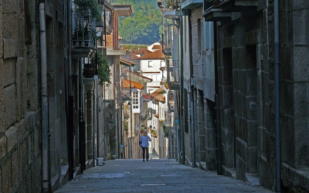 A tourist walking down the historic Jewish quarter of the town of Ribadavia in Spain, September 26, 2016. (Cnaan Liphshiz/JTA)