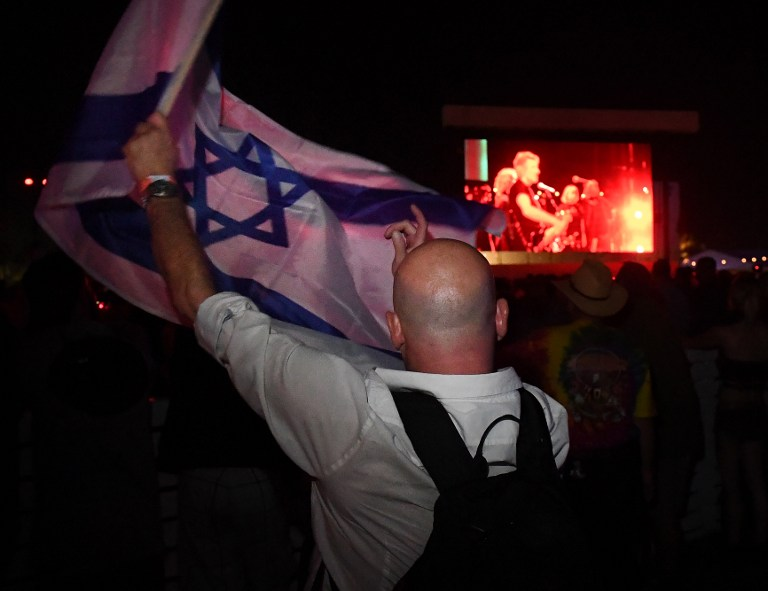 Pro Israel supporter Paul Antey waves the Israeli flag in protest against what he says is the anti-semite political beliefs of artist Roger Waters as he performs on stage during the third day of the Desert Trip music festival at Indio, California on October 9, 2016. (Mark Ralston/AFP)