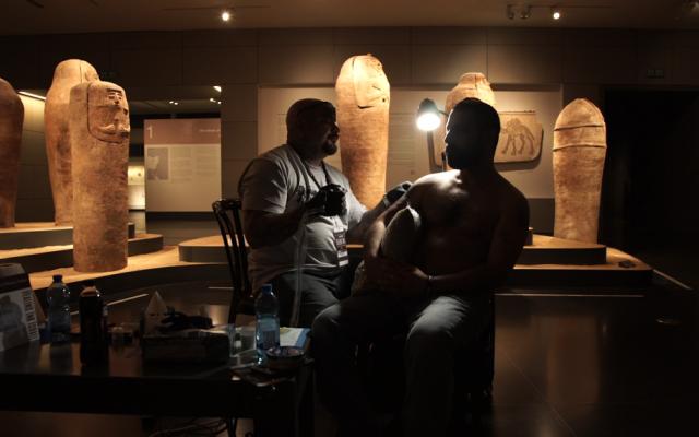 Israeli veteran Barak Miron, injured in Lebanon in 1999, is tattooed by world-famous tattoo artist Steve Soto at the Israel Museum, October 20, 2016. (Luke Tress/Times of Israel)