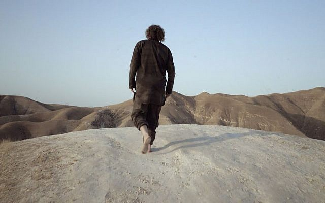 Theo Padnos, wearing the actual clothes he wore as a Nusra Front prisoner, walks in the Judaean Desert (standing in for Syria) during filming of 'Theo Who Lived.' (Zeitgeist Films)