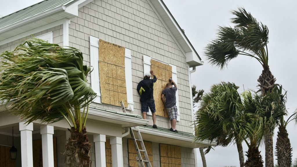 Workers from Armstrong Construction put plywood over windows of a home in preparation for Hurricane Matthew Wednesday, Oct. 5, in Ponte Vedra Beach, Florida. (Will Dickey/The Florida Times-Union via AP)