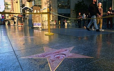 Pedestrians walk past a cordoned off area surrounding the vandalized star for Republican presidential candidate Donald Trump on the Hollywood Walk of Fame, Wednesday, October 26, 2016, in Los Angeles. Detective Meghan Aguilar said investigators were called to the scene before dawn Wednesday following reports that Trump's star was destroyed by blows from a hammer. (AP Photo/Richard Vogel)