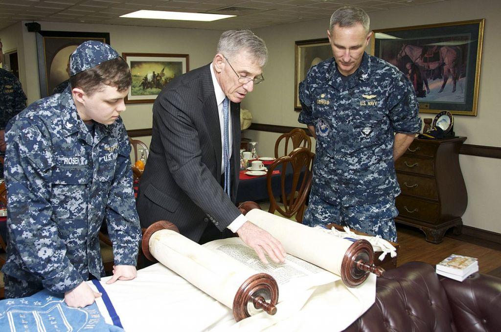 Rabbi Harold Robinson reads the Torah with sailors aboard the USS George Washington. (Public domain)