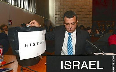 Israel's ambassador to UNESCO Carmel Shama-Hacohen throws a copy of the resolution in the trash on Wed., October 26, 2016. (Erez Lichtfeld)