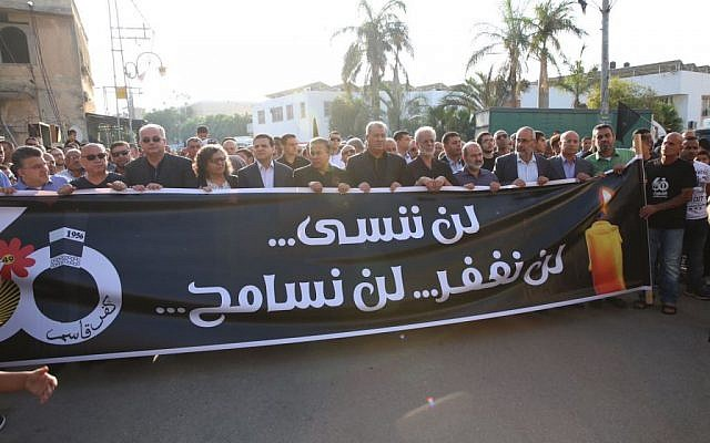Members of the Joint (Arab) List lead a rally in Kafr Kassem, commemorating 60 years since Israeli border police committed a massacre in the village.  The sign reads, 'We will not forget, nor forgive.' (Joint List Spokesperson)