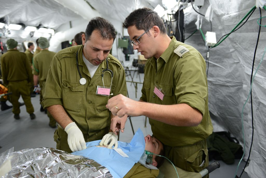 Two IDF doctors perform 'surgery' during a field hospital exercise in Beit Naballah, in central Israel, on December 9, 2013. (IDF Spokesperson's Unit)