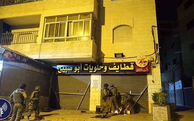 IDF troops in the village of a-Ram, north of Jerusalem, welding iron bars across the entrance of a candy store belonging to the family of a terrorist who killed two Israelis in a shooting spree in Jerusalem earlier in the week, on October 11, 2016. (screen capture of IDF Spokesperson's Unit footage)