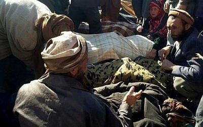 Afghan men and a woman gather around the bodies of civilians, including children, who were allegedly killed by Islamic State (IS) militants in Afghanistan's Ghor province on October 26, 2016. / AFP PHOTO / STRINGER