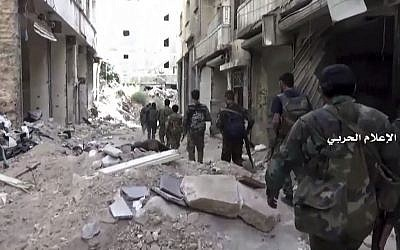 In this still image taken from video provided by the Syrian government-controlled Syrian Central Military Media, government troops patrol inside the Bustan Al-Basha neighborhood of Aleppo, Syria on Tuesday, Oct. 4, 2016. (Syrian Central Military Media via AP)
