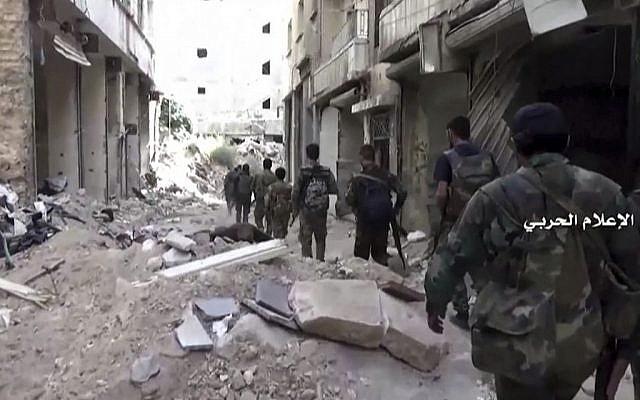 Government troops patrol inside the Bustan Al-Basha neighborhood of Aleppo, Syria, October 4, 2016. (Syrian Central Military Media via AP)