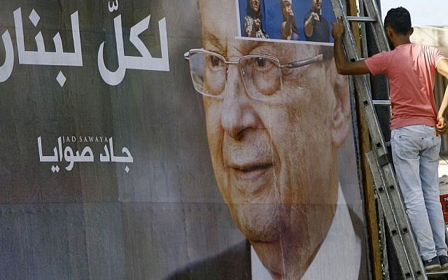 """A worker hangs a billboard showing Christian leader Michel Aoun with Arabic that reads """"For all Lebanon,"""" in the southern port city of Sidon, Lebanon, Sunday, October 30, 2016. for President Bashar Assad in neighboring Syria. (AP Photo/Mohammed Zaatari)"""