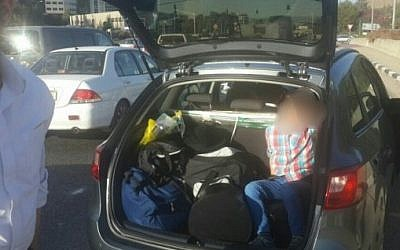 A child sits in the trunk of his family's car after having been placed there by his parents, leading to fears of a kidnapping, October 17, 2016. (Israel Police)