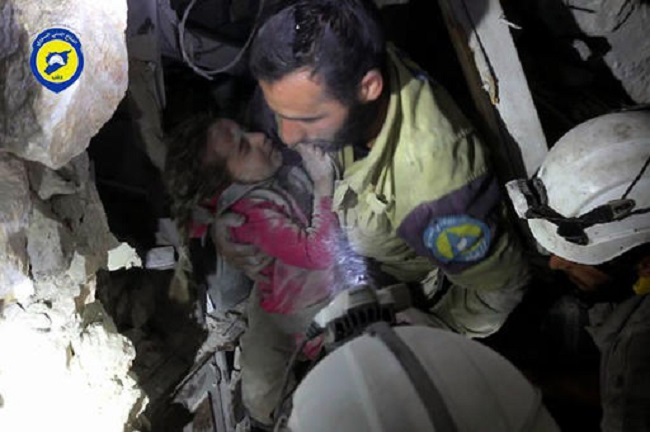 In this Wednesday, Sept. 28, 2016, photo provided by the Syrian Civil Defense group known as the White Helmets, shows a Civil Defense worker carrying a child out from under the rubble after airstrikes hit al-Shaar neighborhood in Aleppo. (Syrian Civil Defense White Helmets via AP)
