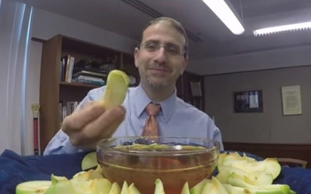 Former US ambassador to Israel Dan Shapiro dips an apple in honey in October 2016 to wish the community a happy Rosh Hashanah. (YouTube screenshot)