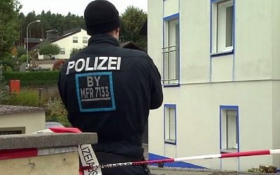A German police officer stands outside the house where a neo-Nazi was arrested in a raid in Georgensmund, Bavaria, October 19, 2016. (Screenshot)