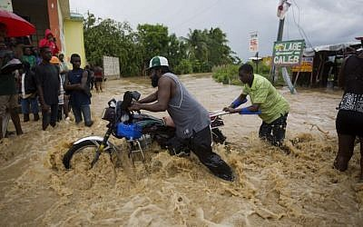 Men push a motorbike through a street flooded by a river that overflowed from heavy rains caused by Hurricane Matthew in Leogane, Haiti, Wednesday, October 5, 2016. (AP Photo/Dieu Nalio Chery)