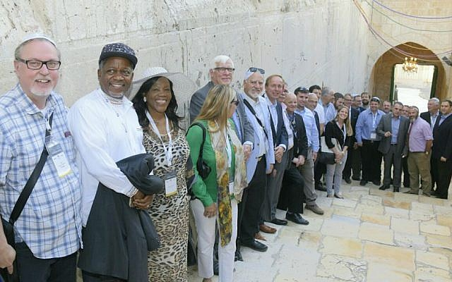 A group of 15 lawmakers from across the world poses for a photo outside the Tomb of the Patriarchs in Hebron, October 19, 2016. (Avi Hayun)