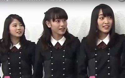 Members of Japanese girl band Keyakizaka46 wearing military-style costumes that were compared to Nazi uniforms. (screen capture: YouTube)