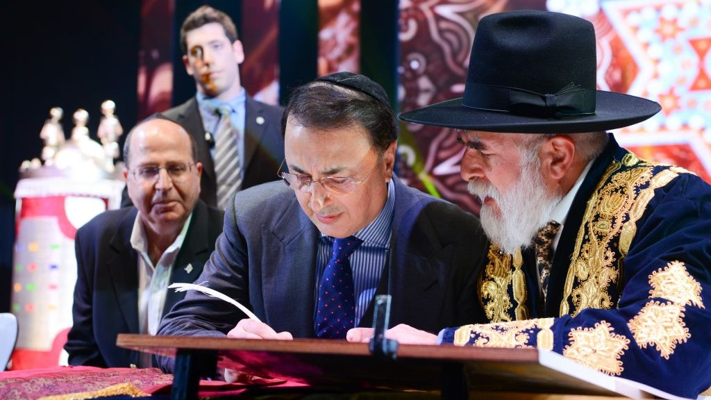 Bukharian billionaire Lev Leviev, center, writing in a Torah scroll with Rabbi Eliyahu Yaakov, right, and Israel's then-defense minister Moshe Yaalon, in Jerusalem, March 23, 2014. (Israel Barddougo/World Congress of Bukhara Jews/JTA)