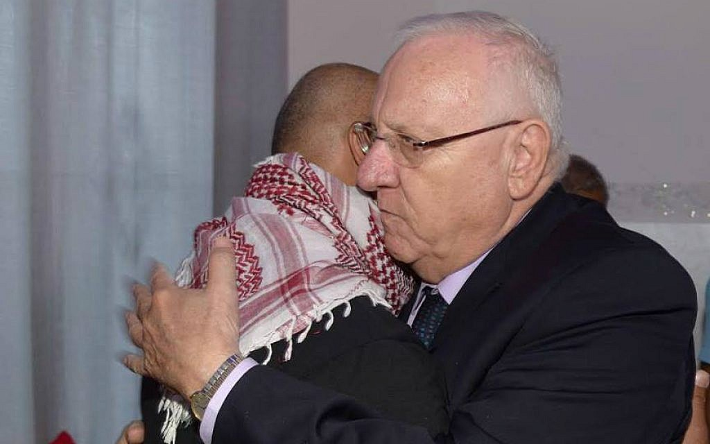 President Reuven Rivlin embraces Bassem Abu Amar, father of Nimer Bassem Abu Amar, 15, who was shot and killed by an Egyptian soldier on October 25, 2016. Rivlin visited the family at their home in Lakiya in southern Israel on October 27. (Mark Neyman/GPO)