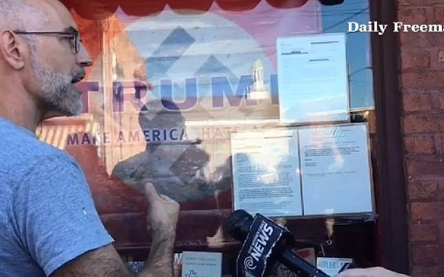 A screenshot from an interview with the owner of the Inquiring Minds Bookstore in upstate New York who displayed the name Trump superimposed over a Nazi flag. (screenshot: Daily Freeman)