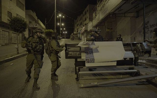 Soldiers removing equipment from a print shop which the IDF said produced posters and other material supporting terror attacks, in al-Ram in the West Bank, October 19, 2016. (IDF Spokesperson)