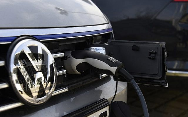 A Volkswagen electric car is plugged in at a power station in Berlin on February 2, 2016. (AFP PHOTO / TOBIAS SCHWARZ)