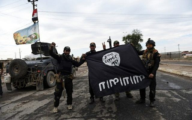 Iraqi soldiers pose with an Islamic State (IS) group flag as they hold a position in the village of Gogjali, a few hundred meters off Mosul's eastern edge, on November 2, 2016, as clashes go on between Iraqi army forces and the jihadists to retake Mosul, the last Iraqi city under the control of IS. (Bulent Kilic/AFP)