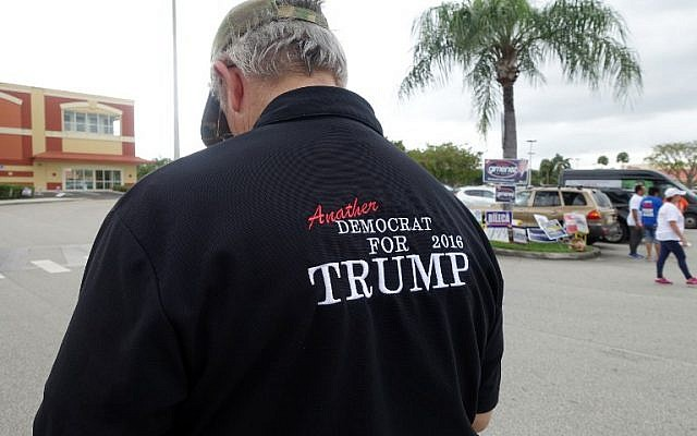 "A man wearing a shirt that reads ""Another Democrat for Trump 2016"" stands outside a Miami library polling place on November 1, 2016, and urges voters to pick Donald Trump for president. Early voting is under way in Miami, including at this library polling place where voters may cast ballots days ahead of the November 8 presidential election (AFP PHOTO / KERRY SHERIDAN)"