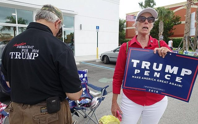 Volunteers Michael Calsetta and Katrina Vidal campaign for US Republican candidate Donald Trump outside a polling place in Miami, on November 1, 2016, in a last-ditch attempt to sway voters before they cast their early ballots in the crucial battleground state of Florida. (AFP PHOTO / KERRY SHERIDAN)