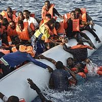Illustrative: Migrants and refugees panic as they fall in the water during a rescue operation of the Topaz Responder rescue ship run by Maltese NGO Moas and Italian Red Cross, off the Libyan coast in the  Mediterranean Sea, on November 3, 2016. (AFP PHOTO/ANDREAS SOLARO)