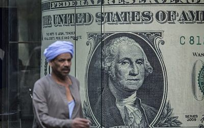 A man walks past a currency exchange shop displaying a giant US dollars banknote in downtown Cairo on November 3, 2016. (AFP PHOTO / KHALED DESOUKI)