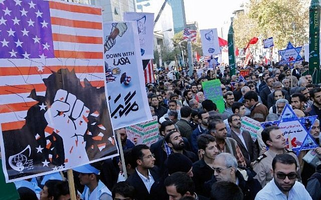 Iranians hold anti-America banners outside the former US embassy in the Iranian capital Tehran on November 3, 2016, during a demonstration marking the anniversary of its storming by student protesters that triggered a hostage crisis in 1979.  (AFP PHOTO / ATTA KENARE)