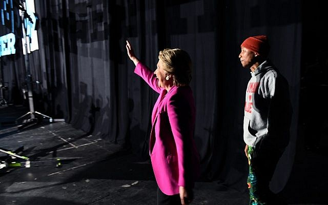 US Democratic presidential nominee Hillary Clinton waves as singer Pharrell Williams follows during a campaign rally in Raleigh, North Carolina, on November 3, 2016. ( AFP PHOTO / Jewel SAMAD)