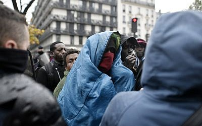 A man wrapped in a blanket stand as migrants wait to climb on a bus during an evacuation of a makeshift camp in Paris on November 4, 2016. (AFP Photo/Philippe Lopez)