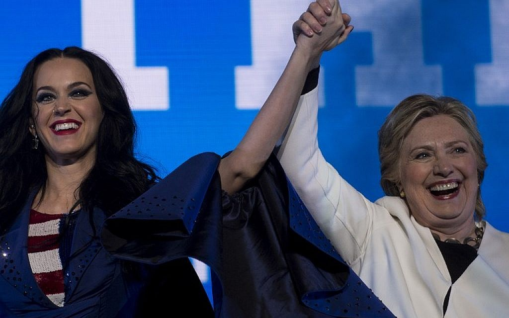 Singer Katy Perry (L) and Democratic presidential nominee Hillary Clinton cheer during a GOTV concert at the Mann Center for the Performing Arts in Philadelphia on November 5, 2016. (AFP PHOTO/Brendan Smialowski)