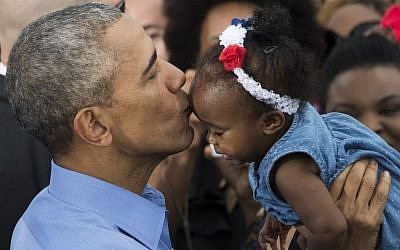 US President Barack Obama holds up a baby after speaking in Kissimmee, Florida as he campaigns for Democratic presidential nominee Hillary Clinton on November 6, 2016 (AFP PHOTO/JIM WATSON)