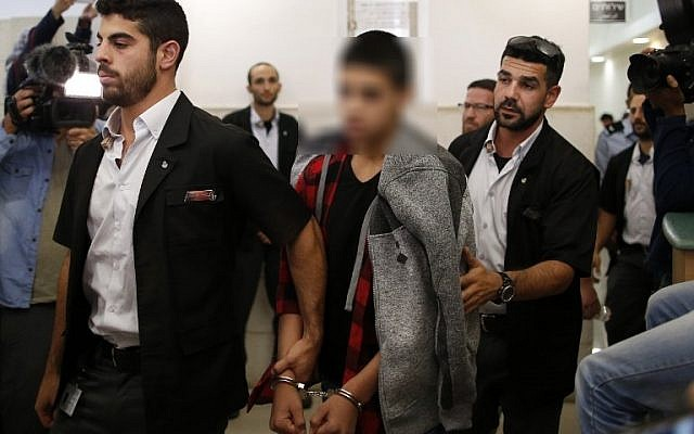 A Palestinian minor, who identity is under court-imposed gag order, convicted of the attempted murder of two Israelis in a stabbing in October 2015, leaves the District Court in Jerusalem after his sentencing hearing on November 7, 2016. (AFP /AHMAD GHARABLI)