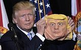 Republican presidential nominee Donald Trump holds a mask of himself which he picked up from supporter during a rally in the Robarts Arena of the Sarasota Fairgrounds in Florida on November 7, 2016.(AFP PHOTO/MANDEL NGAN)