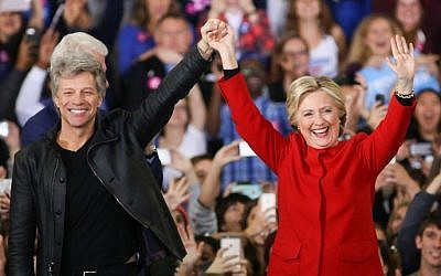 Hillary Clinton and Jon Bon Jovi gesture to the crowd inside the Reynolds Coliseum on the campus of North Carolina State University for the final campaign stop before election day, in Raleigh, North Carolina, on November 7, 2016. (AFP PHOTO / Logan Cyrus)