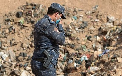 A member of the Iraqi forces checks a mass grave they discovered in the Hamam al-Alil area on November 7, 2016 after they recaptured the area from Islamic State (IS) group jihadists during the ongoing operation to retake Mosul, the last IS-held Iraqi city. (AHMAD AL-RUBAYE / AFP)