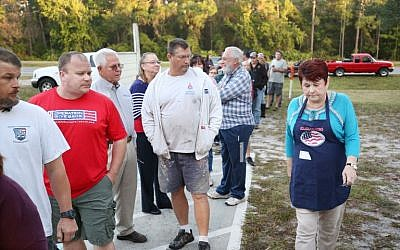 A precinct clerk walks past voters waiting to cast their ballots in the presidential election at a polling station in Christmas, Florida on November 8, 2016. (AFP PHOTO / Gregg Newton)