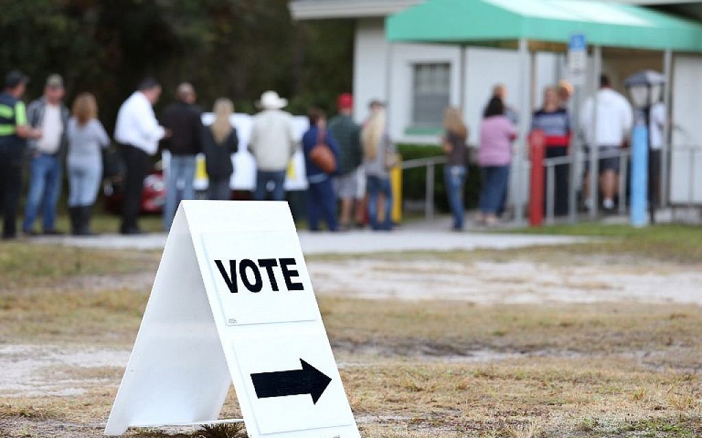 Voters wait in a queue to cast their ballots in the presidential election at a polling station in Christmas, Florida on November 8, 2016. (AFP PHOTO / Gregg Newton)