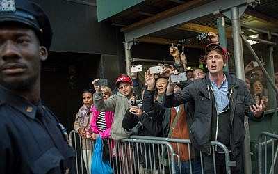 People on the sidewalk cheer and heckle Republican Presidential Candidate Donald Trump as he leaves a polling site on East 56th Street, November 8, 2016 in New York.  (AFP PHOTO / US-VOTE / Bryan R. Smith)
