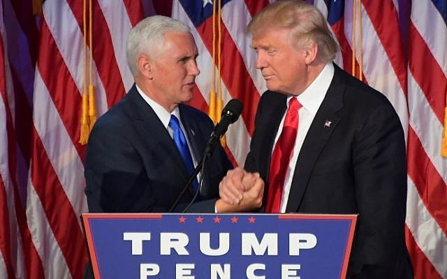 Republican president-elect Donald Trump (R) shakes hands with his running mate Mike Pence at an election victory celebration the New York Hilton Midtown in New York on November 9, 2016.  (AFP PHOTO/JIM WATSON)