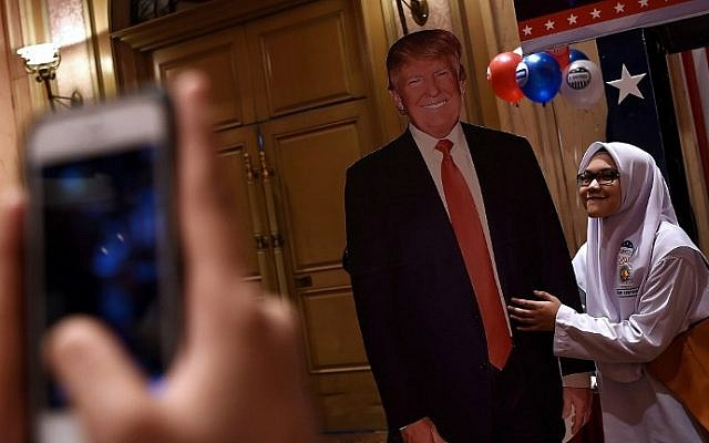 A Malaysian Muslim schoolgirl poses for a photograph with a cut-out of President-elect Donald Trump during an event organized to follow the election results in Kuala Lumpur on November 9, 2016. (AFP/Manan Vatsyayana)