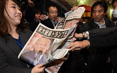 A woman gives out extra editions of a newpaper reporting the victory of Donald Trump in the US presidential election in Tokyo on November 9, 2016. (AFP PHOTO / TORU YAMANAKA)