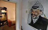 A picture taken on November 9, 2016 shows a large printed photograph of late Palestinian leader Yasser Arafat hanging outside a door leading to a recreation of the small bedroom where he spent his final years at the new Arafat Museum in the West Bank city of Ramallah. (AFP/Abbas Momani)