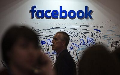 People pass by the stand of Facebook during the Web Summit at Parque das Nacoes, in Lisbon on November 9, 2016. ( AFP PHOTO / PATRICIA DE MELO MOREIRA)