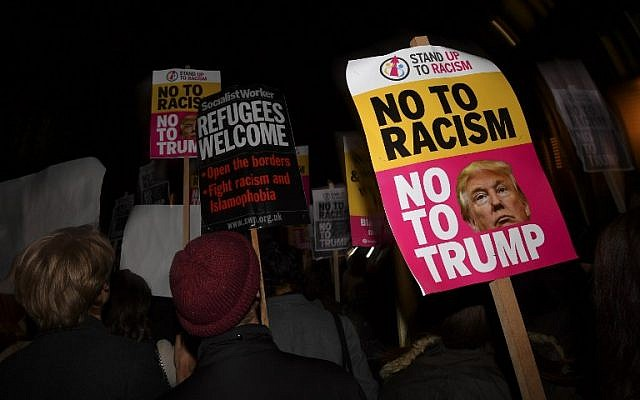 Demonstrators hold placards that read 'No to racism, no to Trump' during a protest outside the US Embassy in London on November 9, 2016 against US President-elect Donald Trump after he was declared the winner of the US presidential election. (AFP PHOTO / BEN STANSALL)